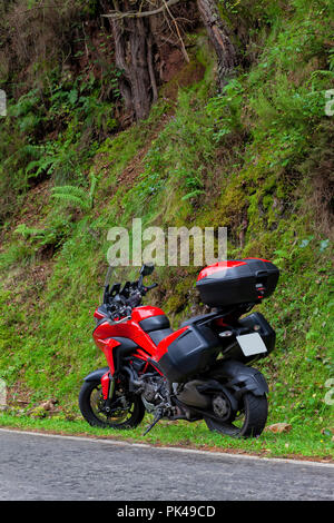 A large red motorcycle parked on the side of the road. - Stock Photo