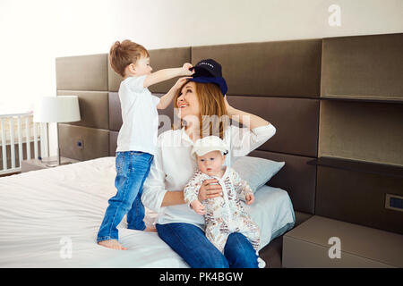 Grandmother with grandsons on the bed in the room.