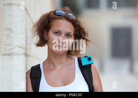 Portrait of redhead woman traveling with backpack and action camera. Looking at the camera while resting near a wall - Stock Photo
