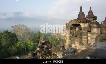Sunrise warming up Buddha in Borobudur Temple - World's Biggest Buddha Temple in Yogyakarta, Indonesia - Stock Photo