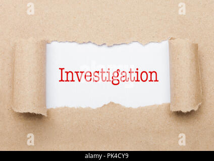 Investigation concept text appearing behind torn brown paper envelope - Stock Photo