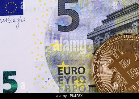 A close up image of a five Euro bill with a golden physical bitcoin - Stock Photo