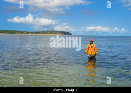 Inhaca island is a small village of 6000 people living only on fishing and tourism.A man doing spear fishing and so many star fishes can be seen befor - Stock Photo