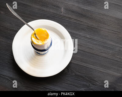 above view of soft-boiled white egg with spoon in cup on plate on dark wooden table with blank copyspace - Stock Photo