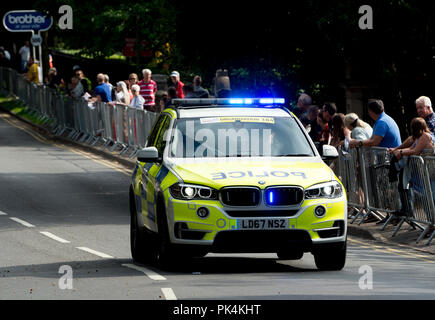 Police car with blue flashing lights at the Tour of Britain cycle race, Leamington Spa, UK - Stock Photo