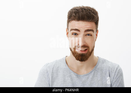 Close up shot of guilty cute boyfriend with beard and brown hairstyle raising eyebrows trying apologize for making mistake saying sorry feeling awkward and confused against white background - Stock Photo