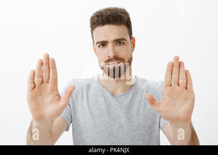 Enough I fed up. Portrait of pressured and displeased masculine and handsome caucasian man with beard and blue eyes raising palms in stop gesture smirking from dislike giving refusal over gray wall - Stock Photo
