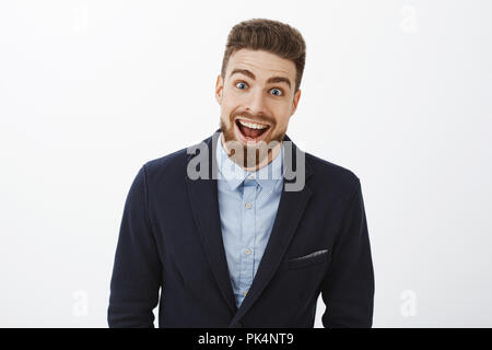 Waist-up shot of enthusiastic delighted and surprised charismatic young rich bachelor in stylish suit with beard and blue eyes smiling broadly from amazement and joy gazing impressed at camera - Stock Photo