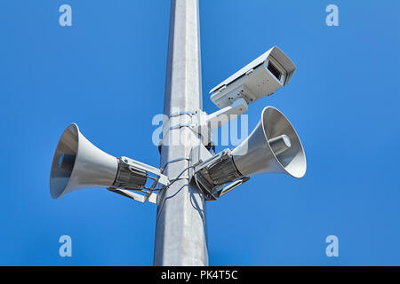 City and road video surveillance system as well as public loudspeakers mounted on a steel pole. - Stock Photo