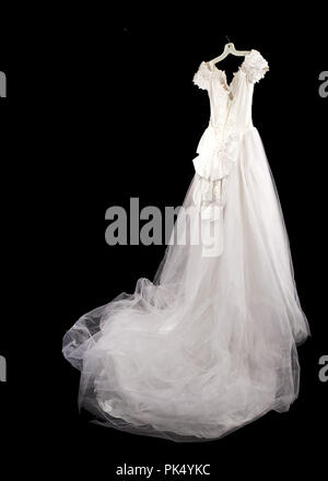 View of the backside of beautiful wedding dress hanging and isolated on black background.  Large bow on back. - Stock Photo