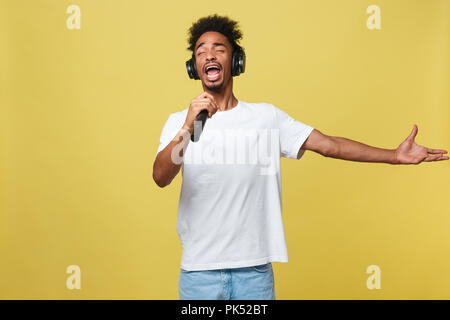 young handsome african american boy singing opera emotional with microphone. - Stock Photo