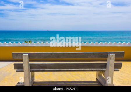 Empty bench on a wooden deck at the shore of beautiful blue sea - Stock Photo