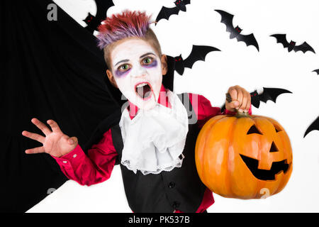 Halloween kids. Spooky Boy with a halloween costume of a vampire Dracula with halloween pumpkin jack o lantern, ready for halloween party or pumpkin p - Stock Photo