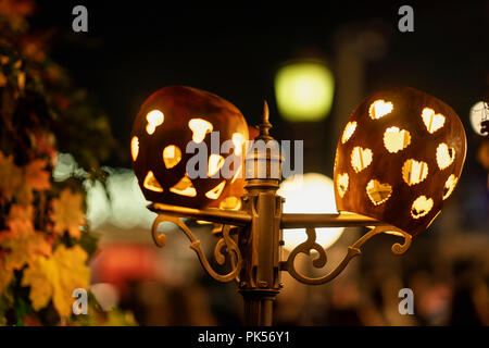 Holidays illumination, electric street lamp decorated with carved pumpkins. Traditional symbol for harvest holidays, Thanksgiving Day, Halloween. - Stock Photo