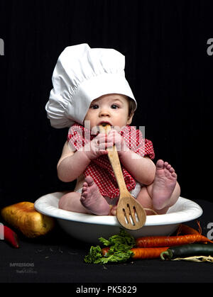 Small baby boy sitting in ceramic bowl with chef's hat on and red plaid scarf around his neck, while eating pasta and /or playing with wooden spoon. - Stock Photo
