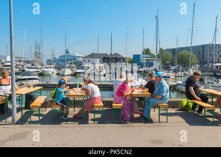 View of people on a summer afternoon eating lunch at tables at the Kalamaja Sunday Market in Tallinn harbor, Estonia. - Stock Photo