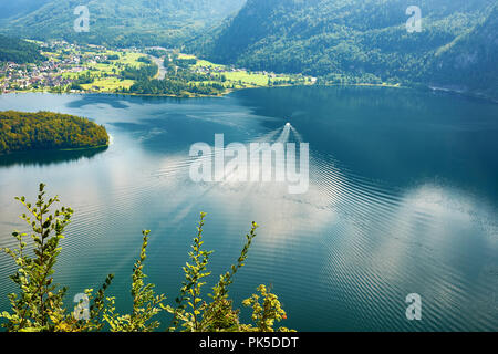 View of Lake, Mountain and Forest at Hallstatt in Austria. A boat sailing on the water - Stock Photo