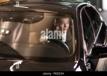 Cheerful chauffeur driving car - Stock Photo