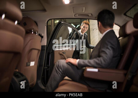 Successful businessman sitting in car back seat - Stock Photo