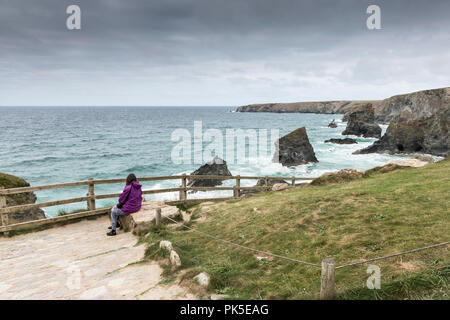 A holidaymaker sitting and looking out over Bedruthan Steps in Cornwall. - Stock Photo