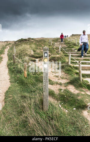 A marker direction post offering alternative routes on the South West Coast Path on the Cornish coast. - Stock Photo