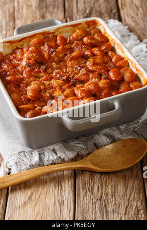 Serbian food: prebranac baked beans with onion close-up in baking dish on a table. vertical - Stock Photo