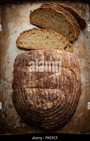 Fresh bread being sliced on a rustic background - Stock Photo