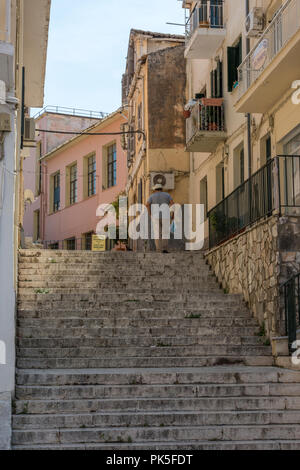 an elderly or older greek gentleman walking up a large flight of steps or stairs in the historic old town of kerkyra, corfu, greece. - Stock Photo