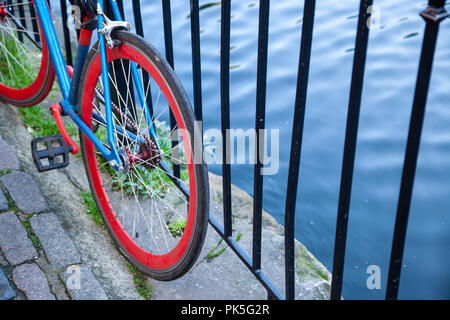 Bicycle with bright blue frame and red wheels leaning against railings beside a canal. - Stock Photo