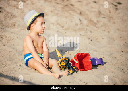 Cute little toddler boy sitting and playing children's beach toys on beautiful sandy  beach, Family travel, water outdoor activity on beach vacation c - Stock Photo