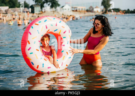Mom and daughter having fun in the water with  inflatable donut. Summer holiday - Stock Photo