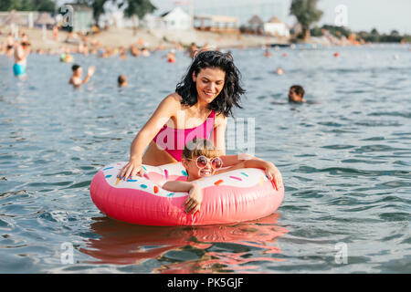 Mom and daughter swiming and relaxing in the water on an inflatable donut. Summer holiday - Stock Photo