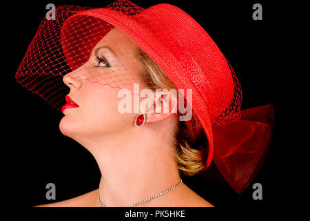 Lady wearing red retro hat with small veil and hat alone in one image.  Both isolated on black background. - Stock Photo