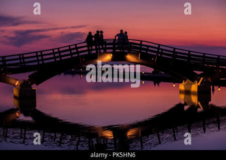 Silhouettes and reflections as tourists enjoying a beautiful sunset over the marina bridge in Lefkada, Greece - Stock Photo
