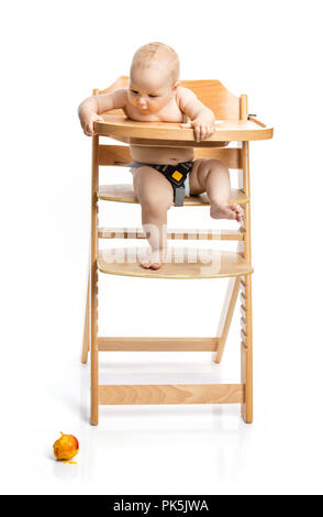 Cute baby girl looking at peach she dropped while sitting in high chair over white - Stock Photo