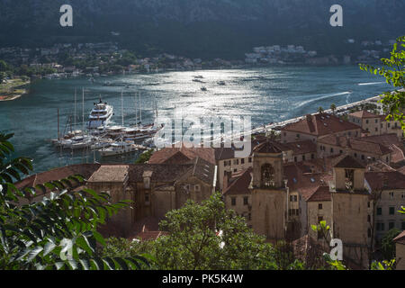 Elevated view of the historical medieval walled town of Kotor in Montenegro showing boats / yachts in port and sun reflecting on the water of the Bay. - Stock Photo