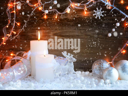 Two burning candles with a deer on snow and christmas lights