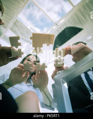 bottom view. business team folding puzzle pieces. . - Stock Photo