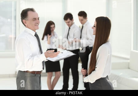 senior businessman discussing a financial report with the employee - Stock Photo