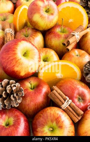 Composition of apples, cinnamon sticks, orange slices, and pine cones. Shallow dof. - Stock Photo