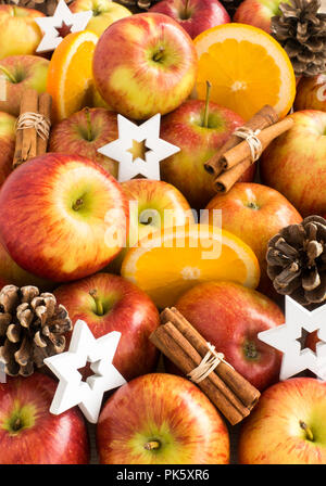 Composition of apples, oranges, cinnamon sticks, pine cones and white wooden christmas stars. Shallow dof. - Stock Photo