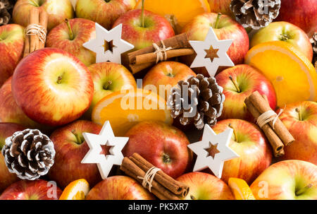 Composition of apples, cinnamon sticks, orange slices, pine cones and white wooden christmas stars. Shallow dof. - Stock Photo