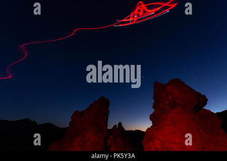 Light painting and drawing with red torch, alien spaceship flying in over the red rocks of the volcanic landscape on Teide national park at dusk, Tene - Stock Photo