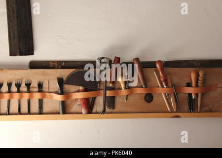 Leather working tools hanging on a shelf at the Volkening Heritage Farm in Schaumburg, Illinois on a late summer day. - Stock Photo