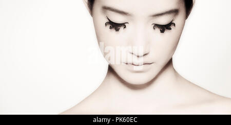 A beautiful girl looking down revealing her stunning seahorse shaped eyelashes. - Stock Photo
