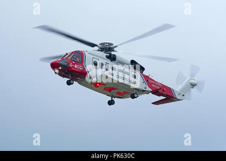 The Inverness based HM Coastguard SAR helicopter leaving its base as it heads West on a mission down to Fort William in Lochaber district. - Stock Photo