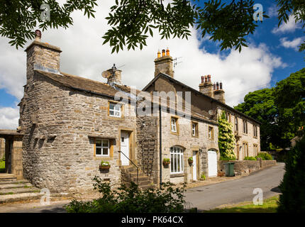 UK, Yorkshire, Horton in Ribblesdale, house with curved wall beside church lychgate - Stock Photo