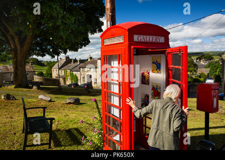 UK, Yorkshire, Settle, Green Head Lane, visitor looking into the Gallery on the Green, in old red K6 phone box, world's smnallest art gallery - Stock Photo