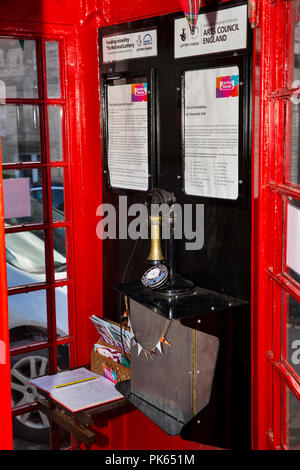 UK, Yorkshire, Settle, Duke St, Gallery with audio on old candlestick telephone, in old red K6 phone box - Stock Photo