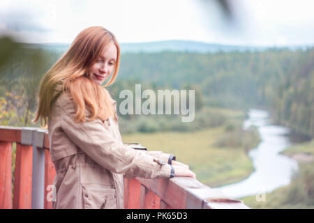 Girl traveler with red long hair standing on observation deck an - Stock Photo